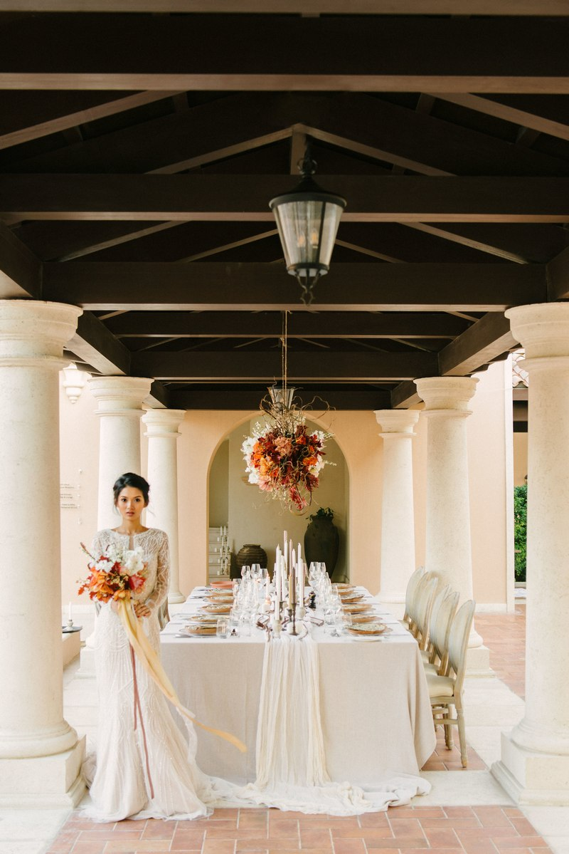 Bride standing holding bouquet in front of elegant wedding table