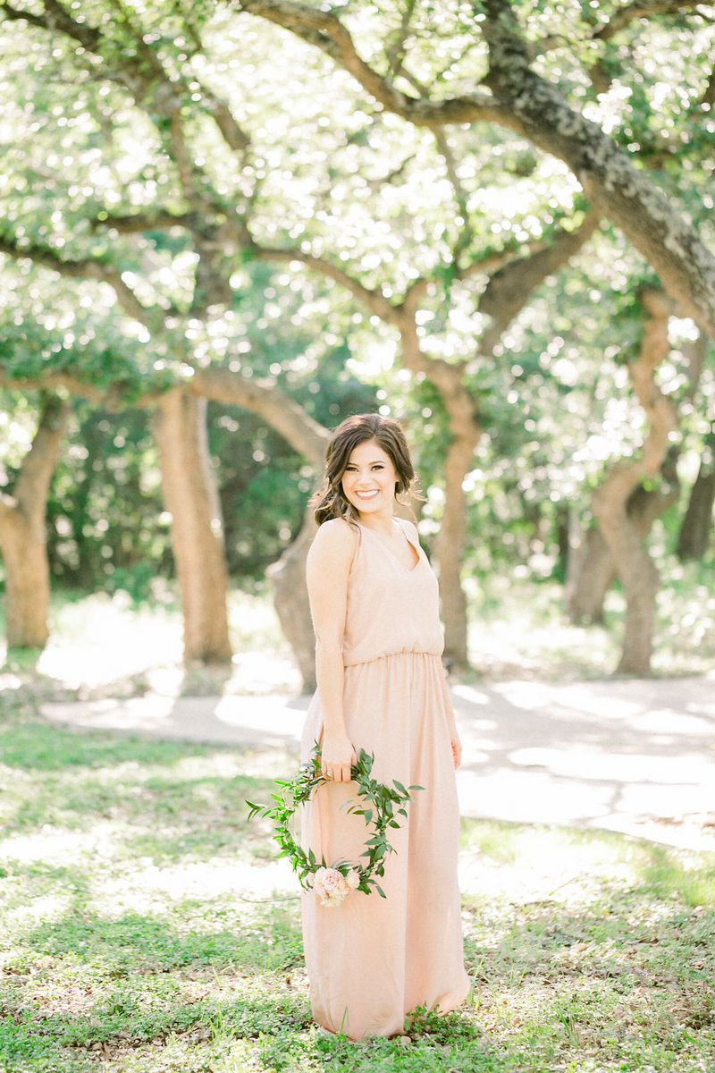 Bridesmaid in peach dress holding foliage hoop