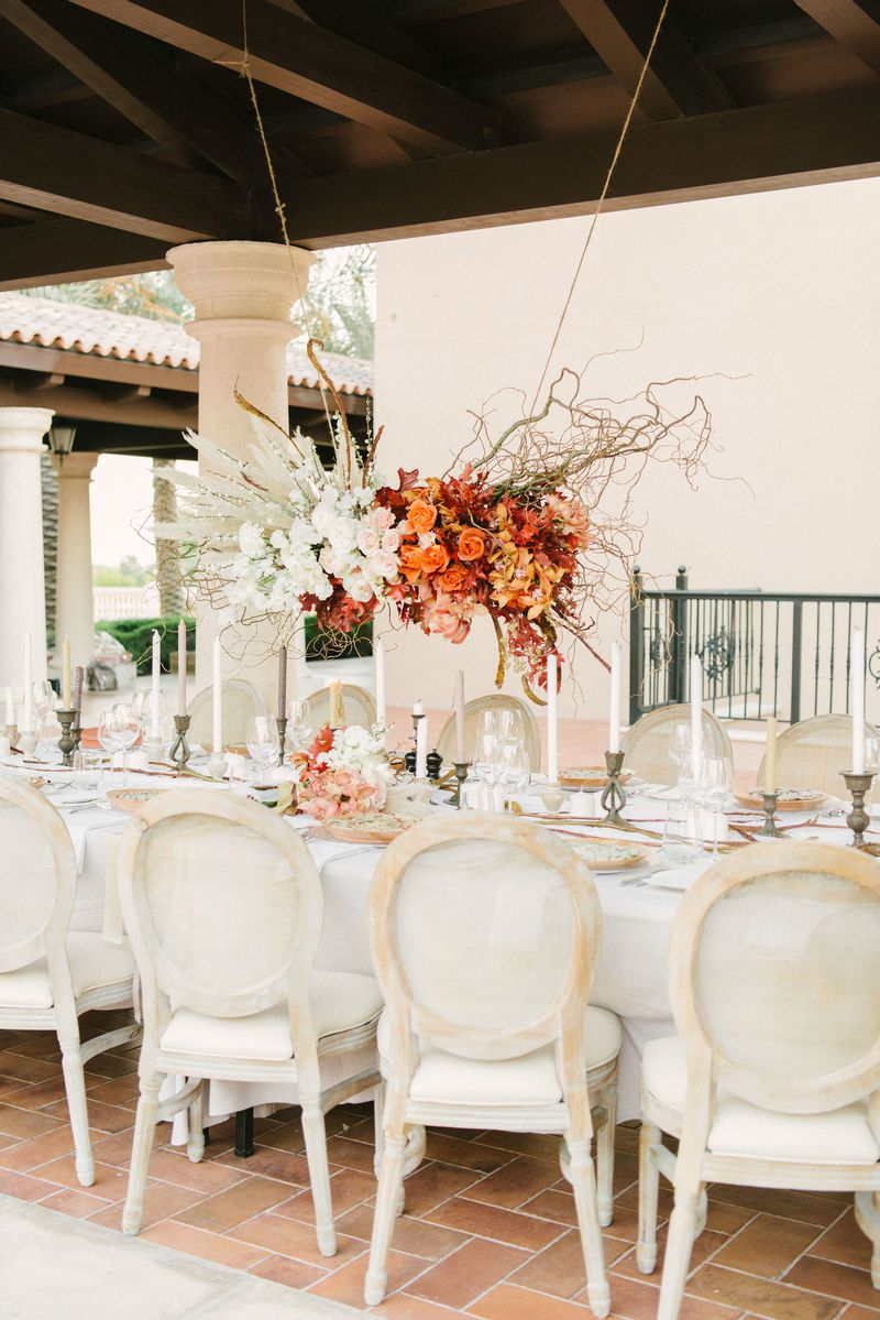 Autumnal floral installation hanging above wedding table