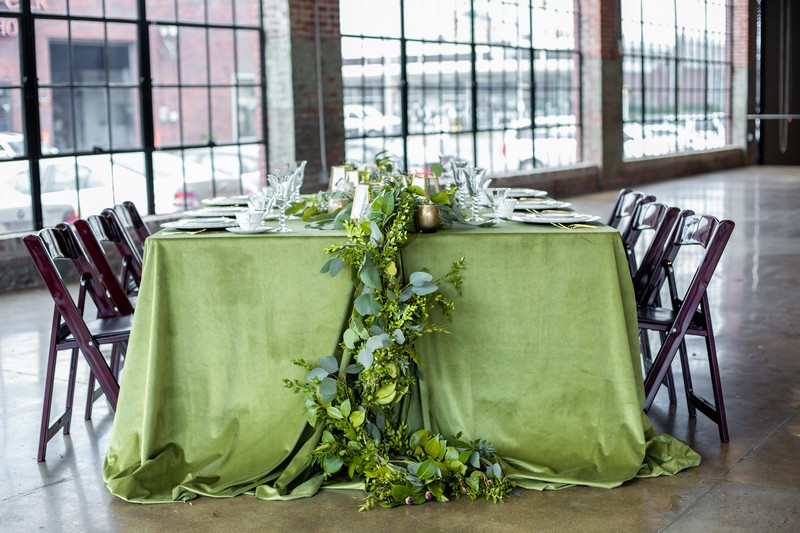 Foliage hanging off end of wedding table with green tablecloth