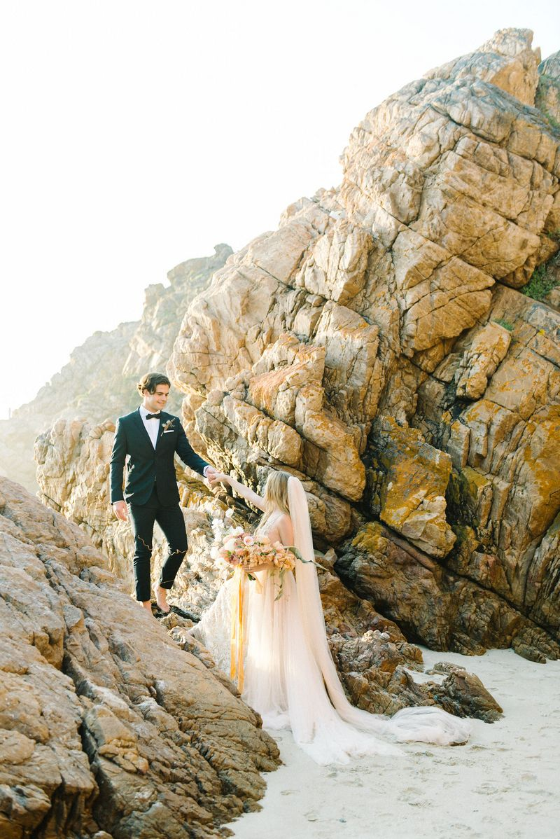 Groom holding bride's hand to help her up onto rocks on beach