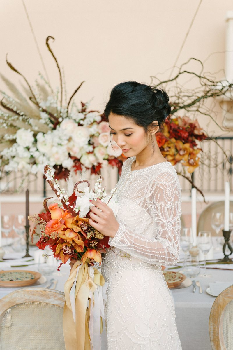 Bride holding autumnal bouquet in front of elegant wedding table