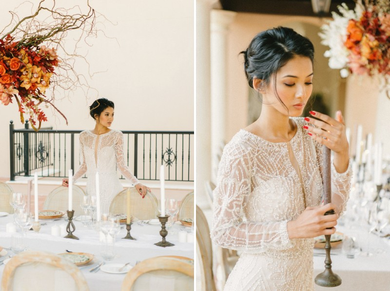 Bride holding candle next to wedding table