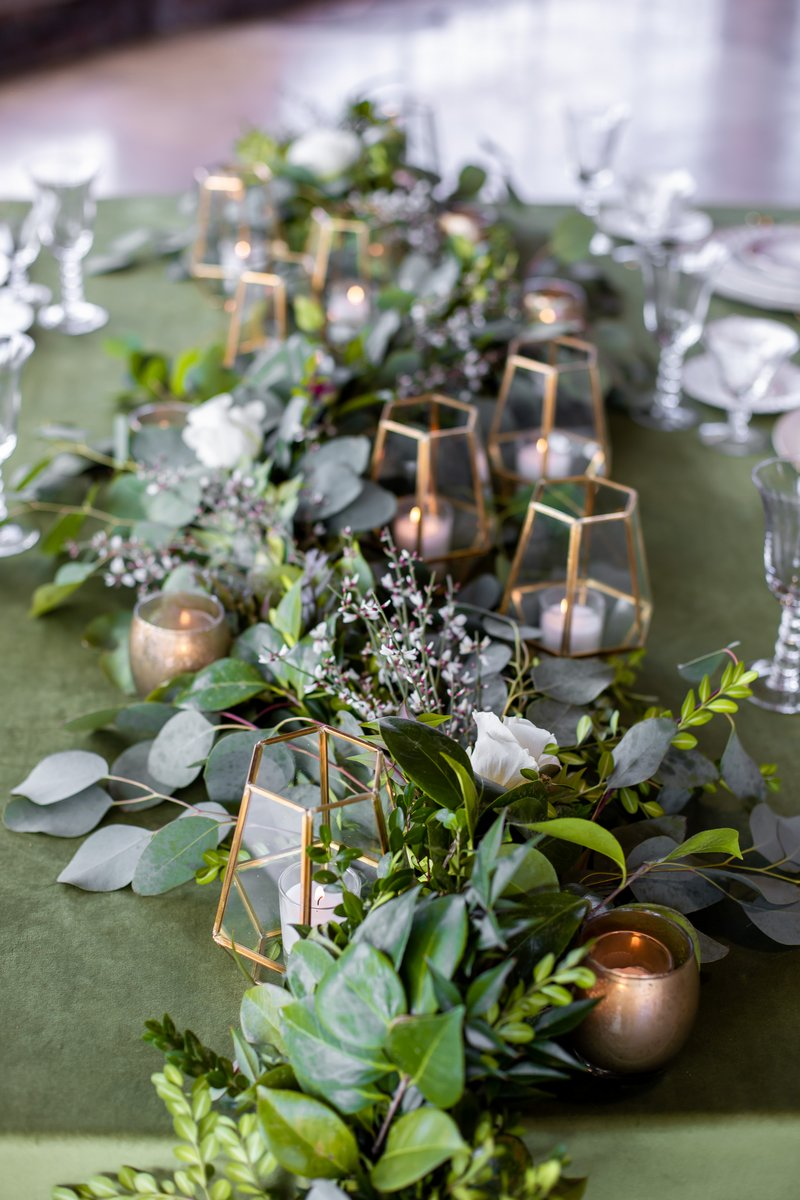 Foliage wedding table runner with gold lanterns and votives