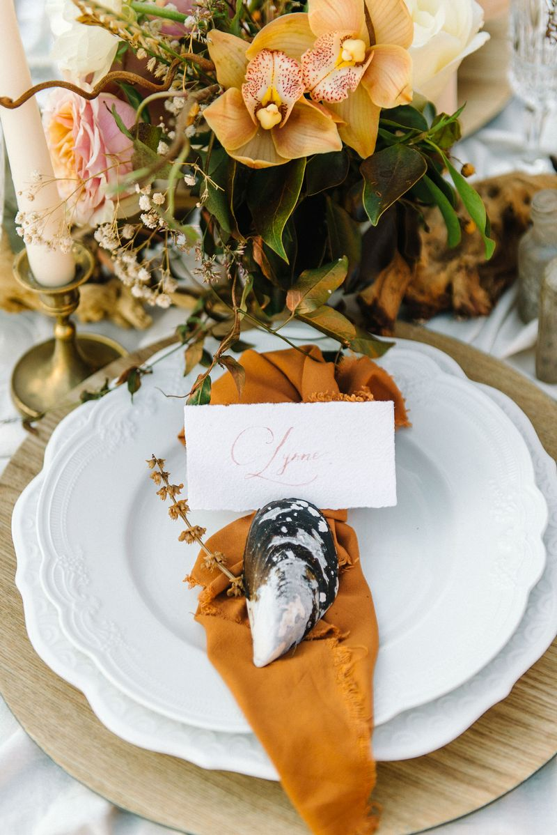 Wedding place setting with rust coloured napkin and sea shell