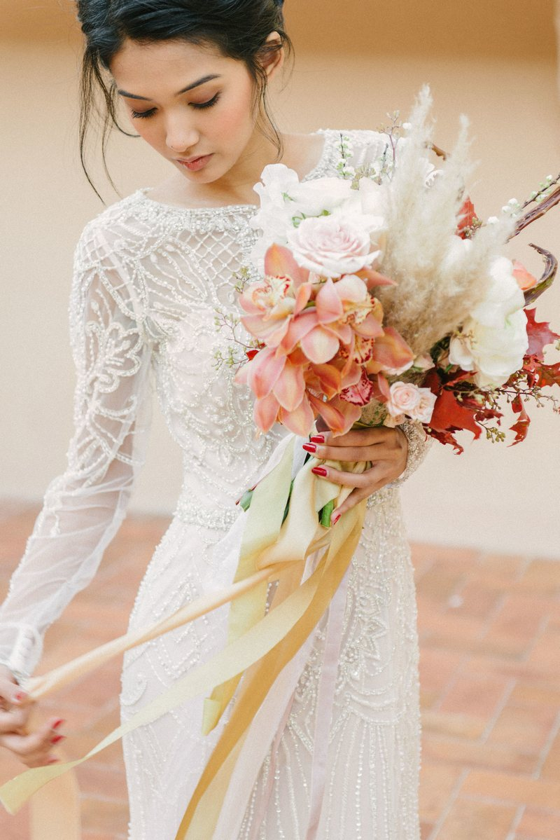 Bride holding elegant, autumnal wedding bouquet