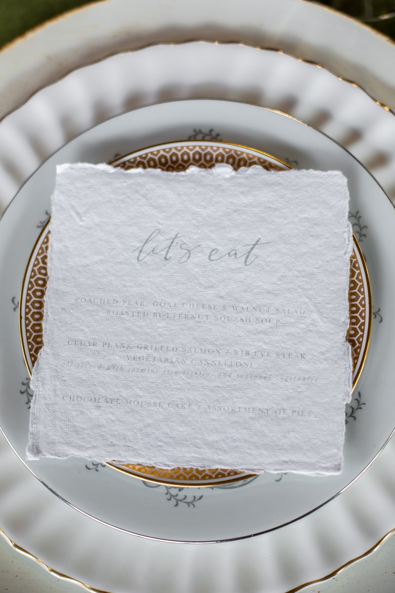 Wedding menu on top of plate with gold pattern