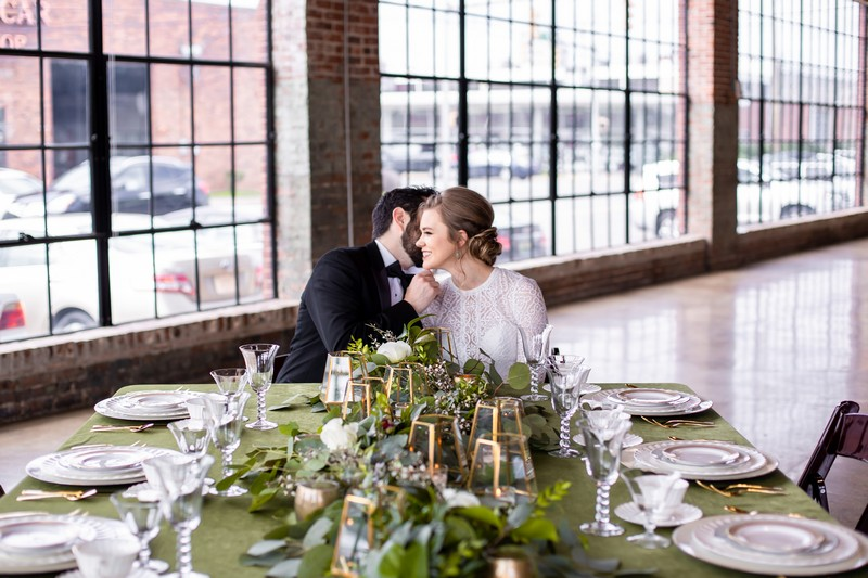 Bride and groom sitting at wedding table with foliage runner