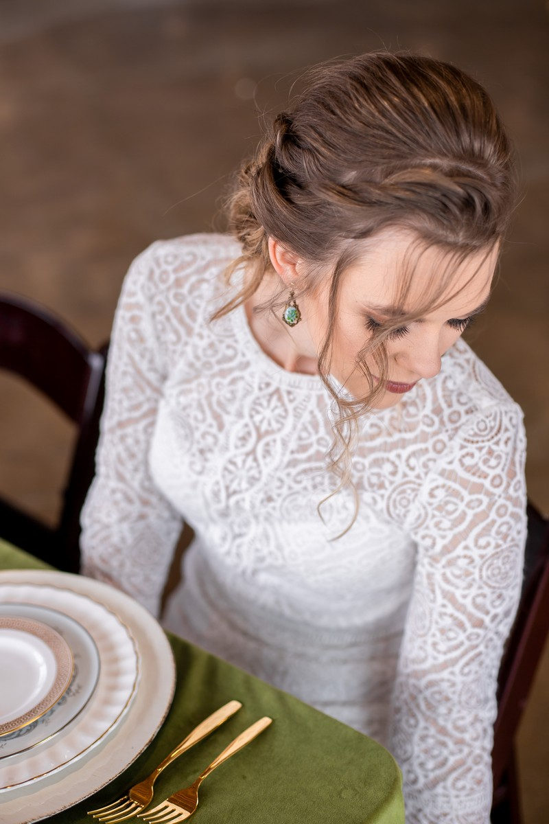 Bride with updo hairstyle sitting at wedding table