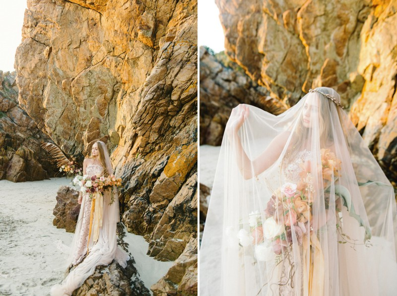 Bride standing on rocks on beach with veil over her face