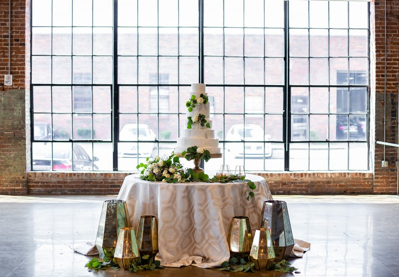 Wedding cake table dressed with foliage and gold lanterns