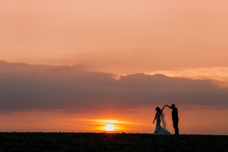 Bride twirling under groom's arm as sun sets in background - Picture by John Hope Photography