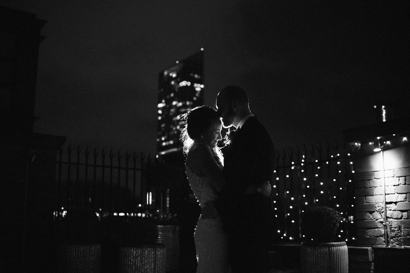 Bride and groom hugging at night with tall building in background - Picture by Rebecca Parsons Photography