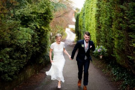 Groom grimacing as he walks up steep hill with bride - Picture by Carine Bea