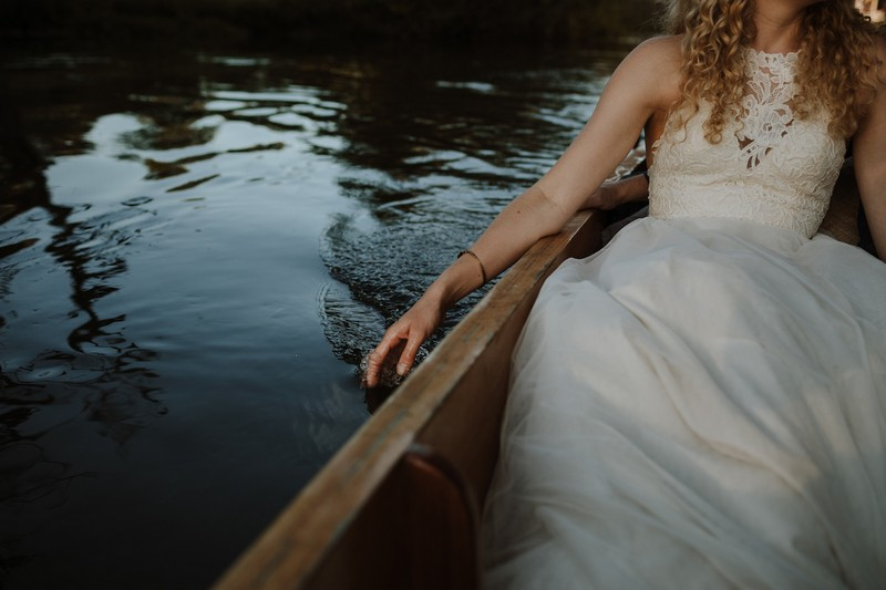 Bride sitting in boat with hand in the water - Picture by Caro Weiss Photography