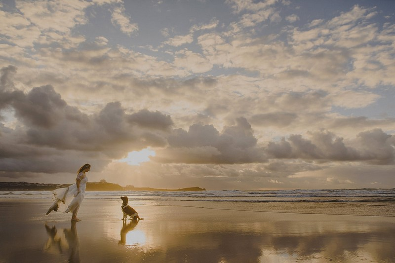 Dog sitting in front of bride on beach - Picture by Abi Riley Photography