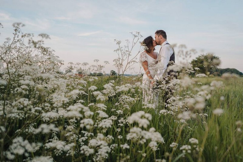 Bride and groom kissing in field of white flowers - Picture by Mr & Mrs