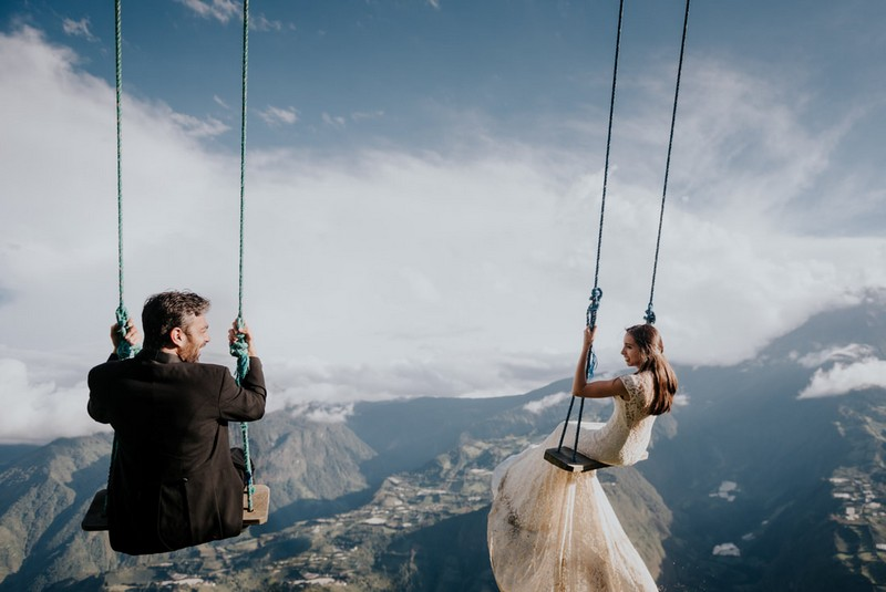Bride and groom sitting on swings overlooking mountains - Picture by Daniel Maldonado Photography