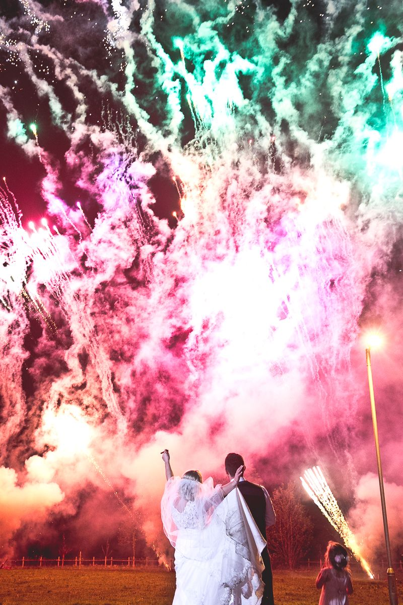 Bride and groom watching colourful fireworks display - Picture by Katie Sidell Photography