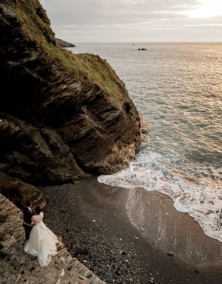 Bride and groom next to cliff near Tunnels Beaches looking out to sea - Picture by Robin Goodlad Photography
