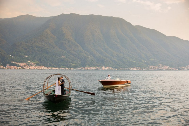 Bride and groom standing kissing on rowing boat - Picture by Damion Mower Photography