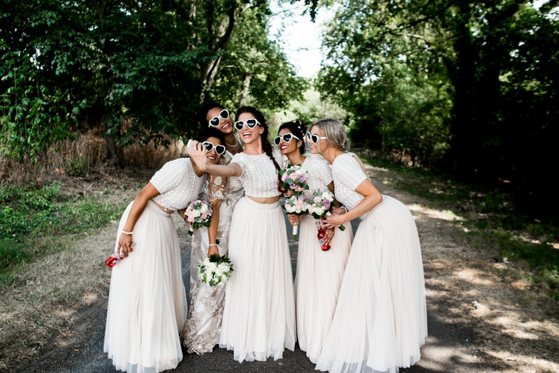 Bridesmaids in white dresses and heart sunglasses taking a selfie - Picture by Nicola Norton Photography