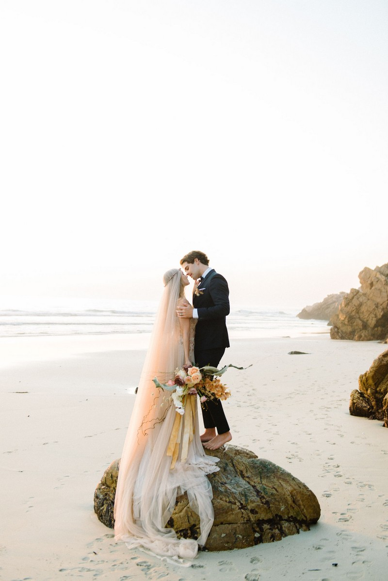 Bride and groom standing on rock on beach
