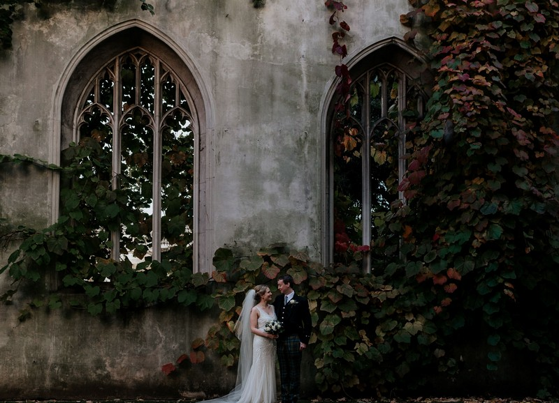 Bride and groom standing in front of St Dunstan Chapel ruins - Picture by Emily Black Photography