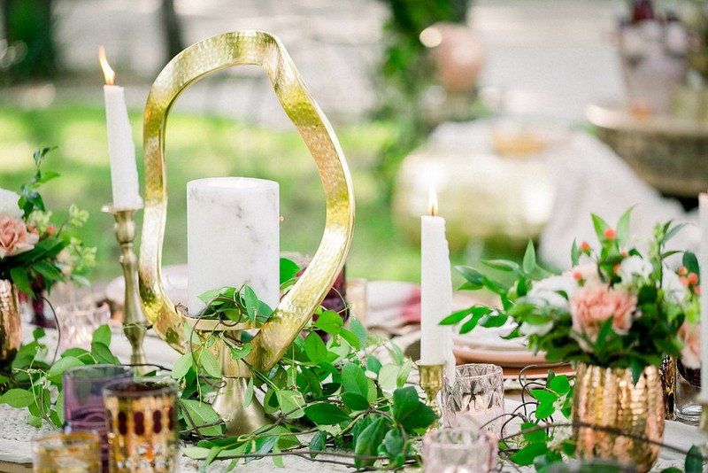 Foliage, candles and gold ornament on table