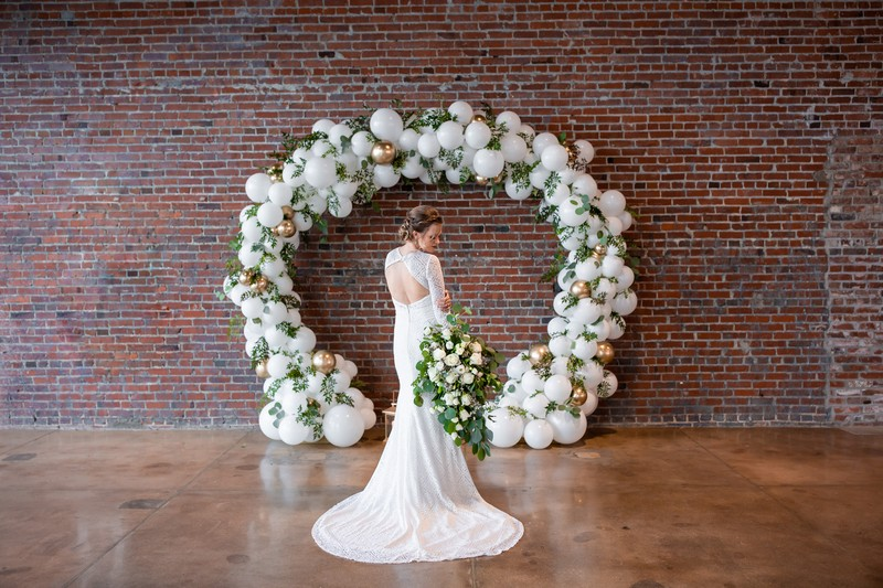 Bride standing in front of white balloon arch with foliage