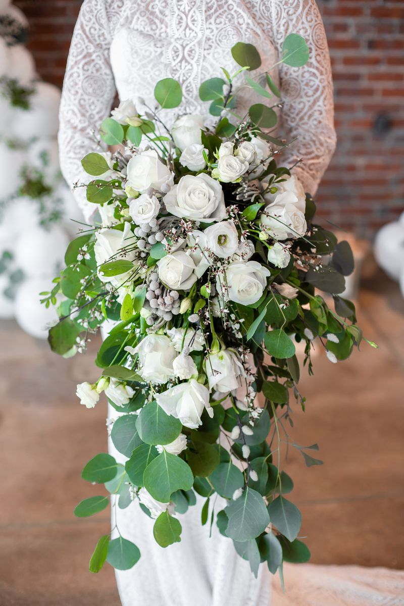 Bride holding cascading bouquet with white roses and green foliage