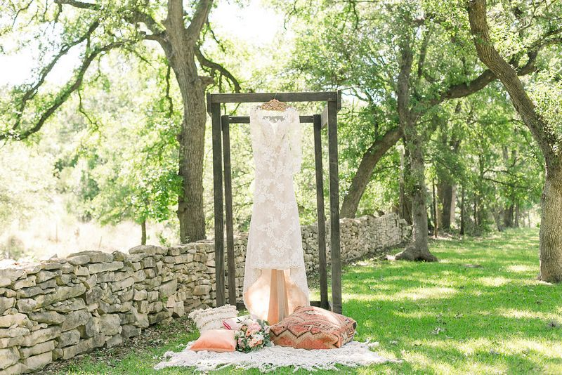Wedding dress hanging over patterned cushions