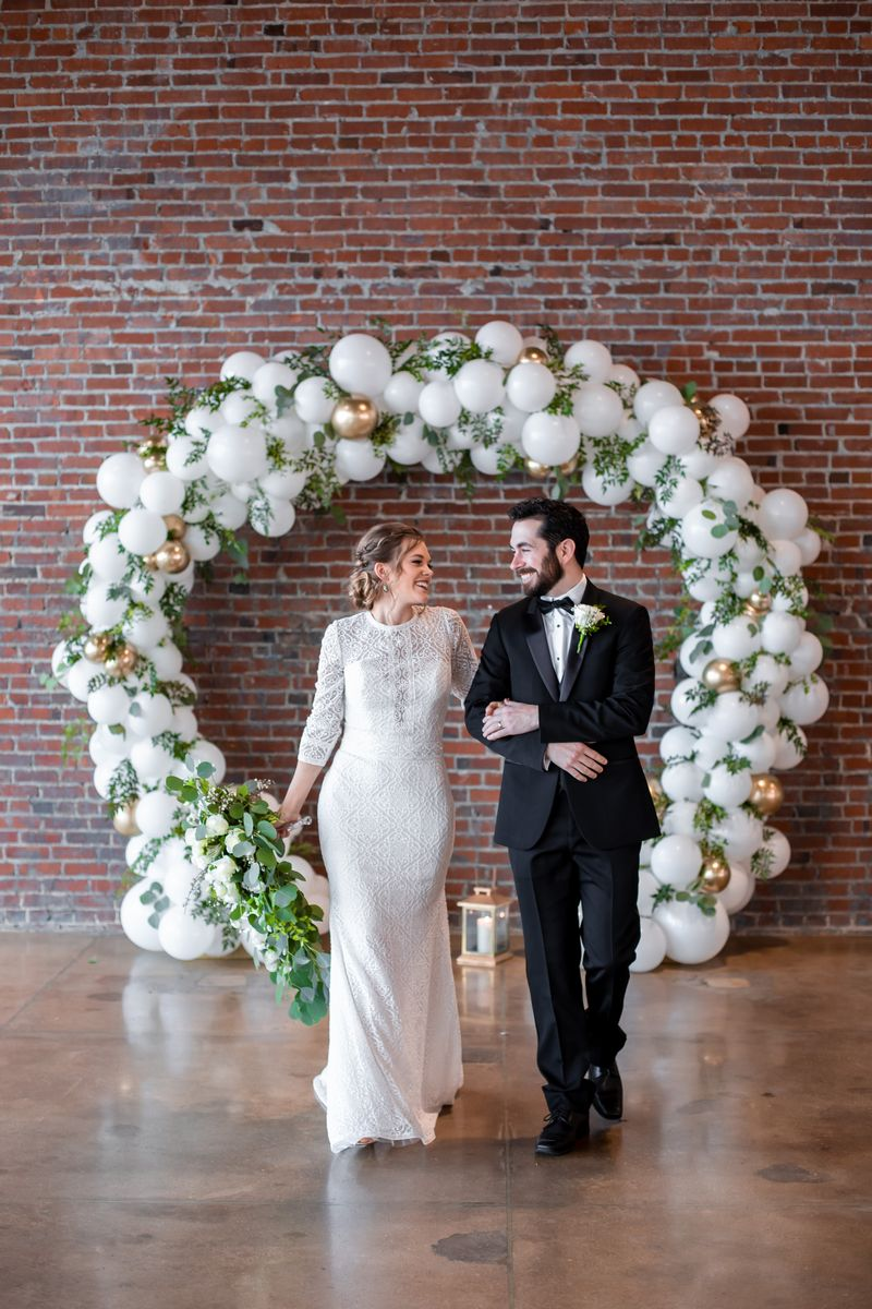Bride and groom in front of balloon arch
