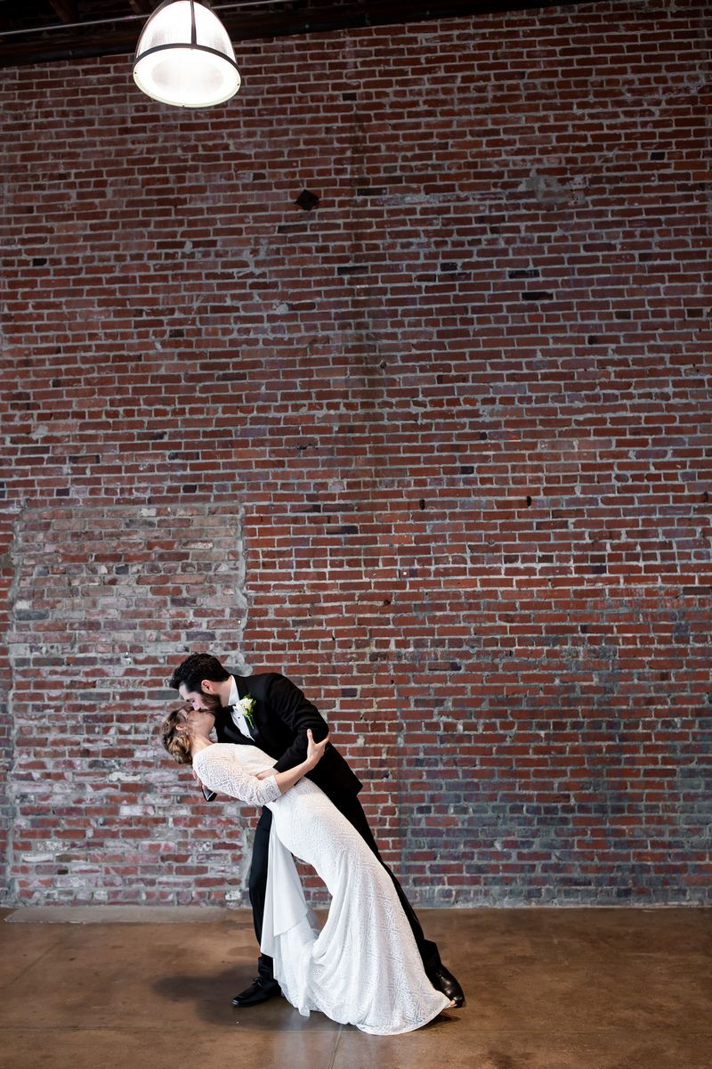 Groom leaning bride back to kiss her