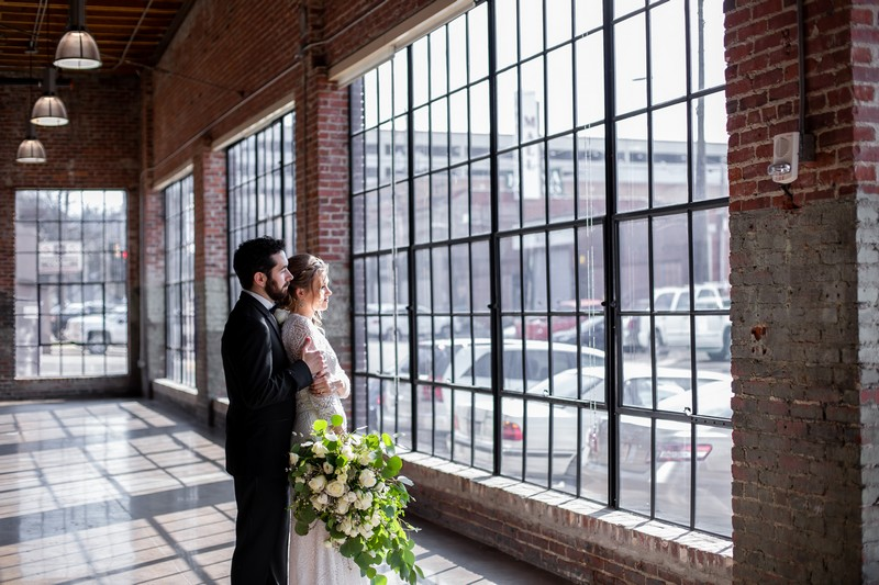 Bride and groom looking out of large windows at Events at Haven