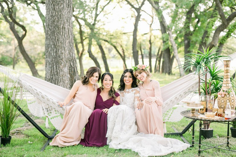 Bride-to-be and bridesmaids sitting in hammock