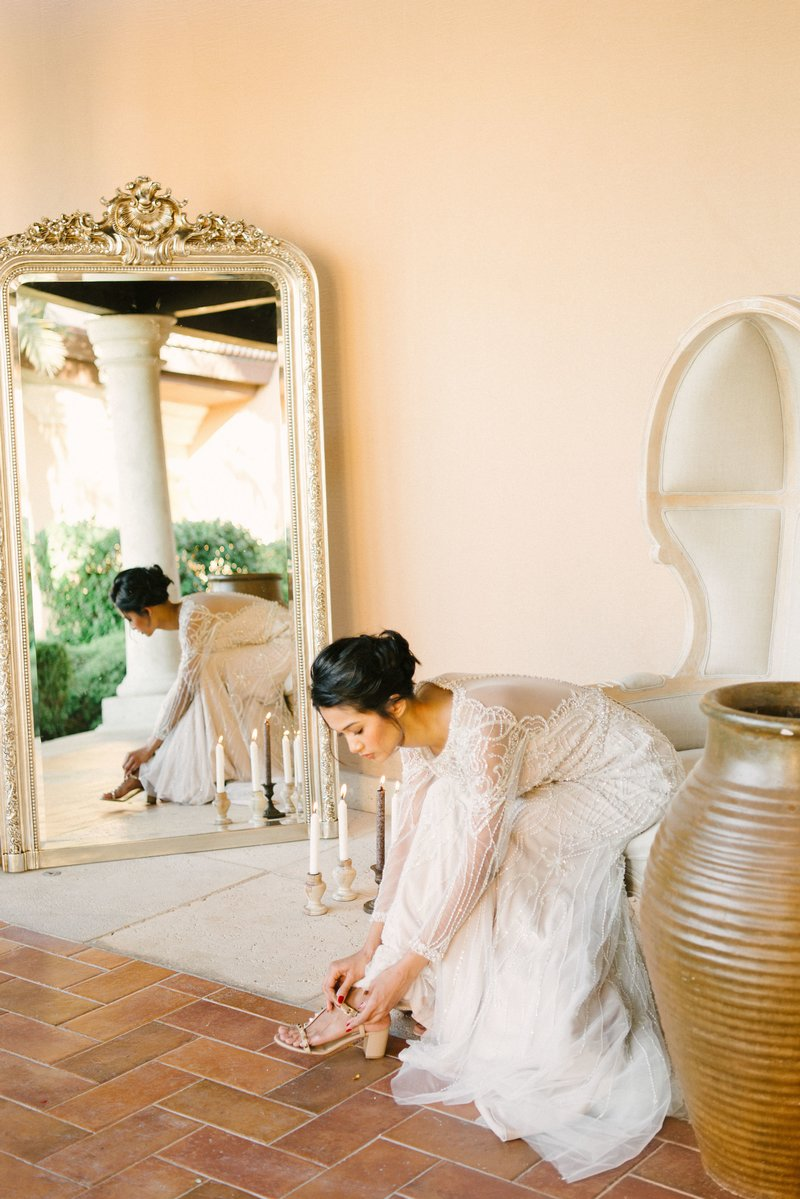 Bride leaning forward from chair to put on bridal shoes