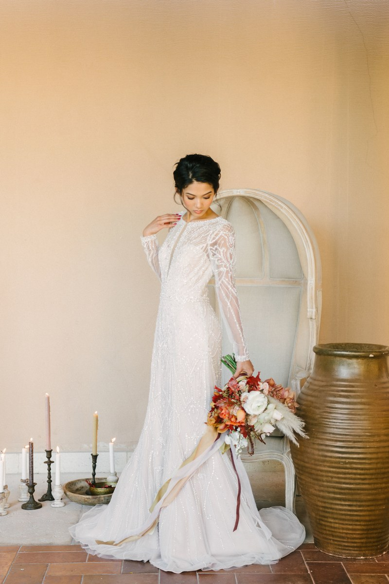Bride holding bouquet in front of chair