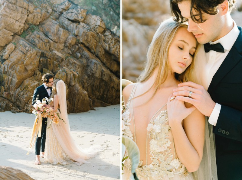 Bride and groom on beach by rocks