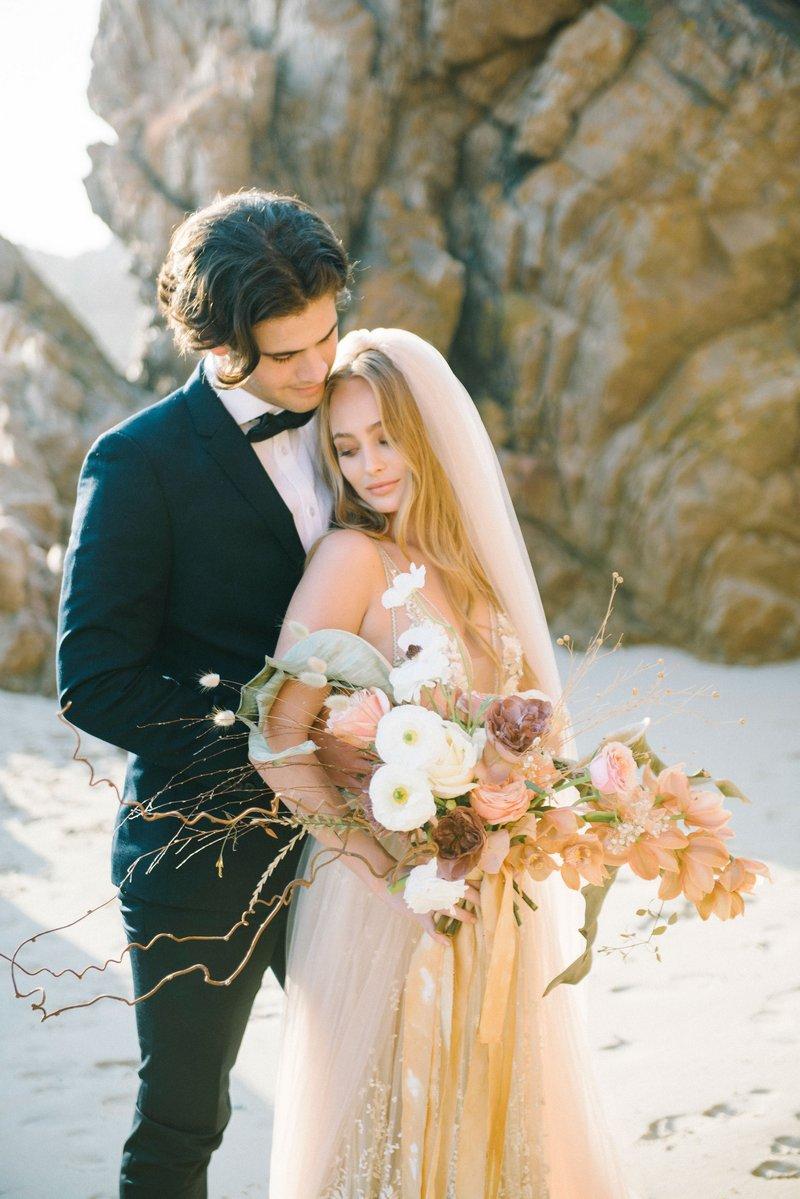 Groom standing behind bride on beach