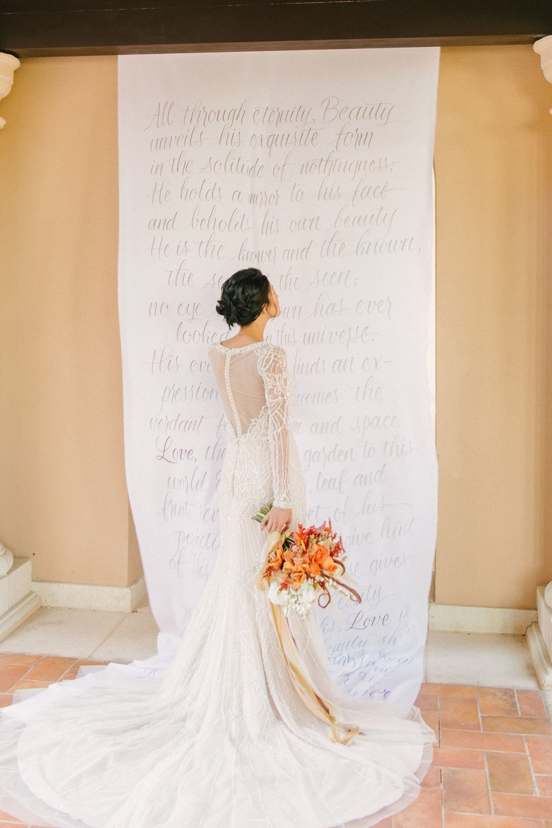Bride standing in front of long material backdrop with writing on it