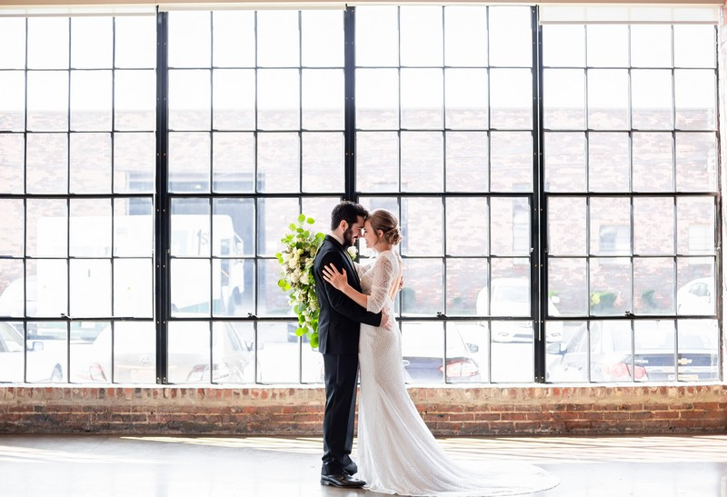 Bride and groom in front of large windows at Events at Haven