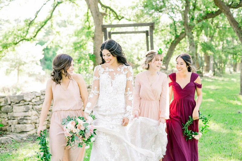 Bride-to-be walking with bridesmaids carrying foliage hoops