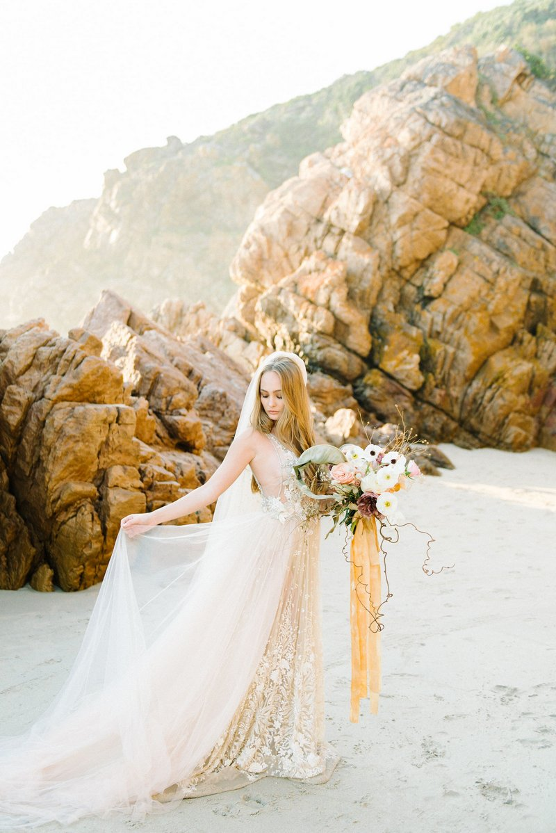 Bride holding out skirt of her wedding dress on beach