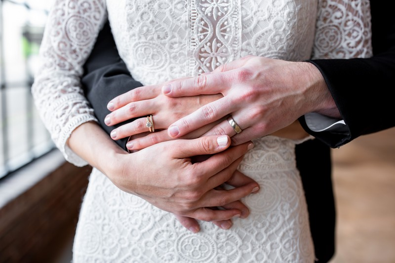 Bride's hands on top of groom's around her waist