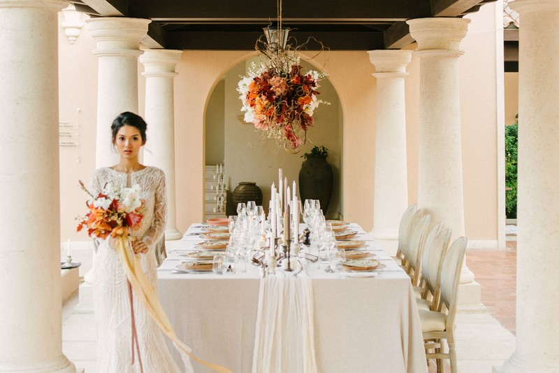Bride standing by elegantly styled wedding table