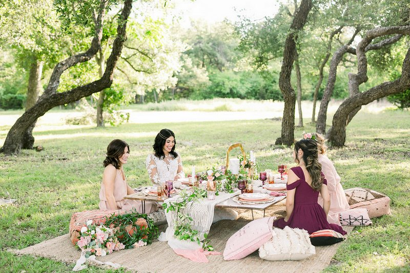 Bride-to-be and bridesmaids sitting around a low-level table for bridal shower