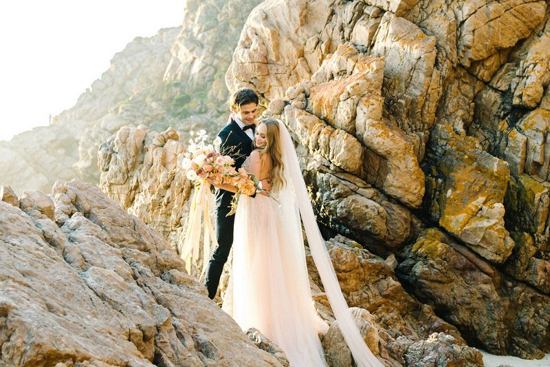 Bride and groom standing on rocks on beach