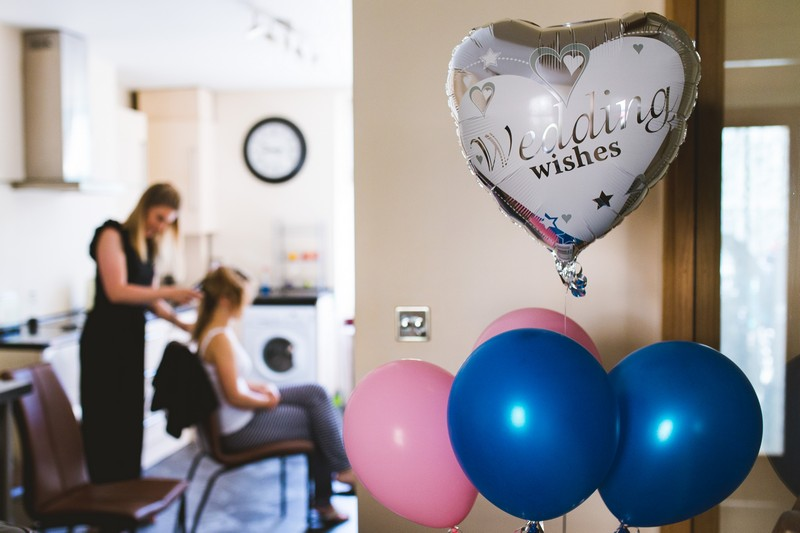 Wedding balloons with bride having hair done in background