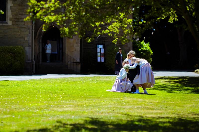 Young bridesmaids hugging outside church